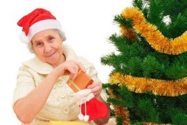 happy grandma in Santa cap decorating Christmas gifts on white background